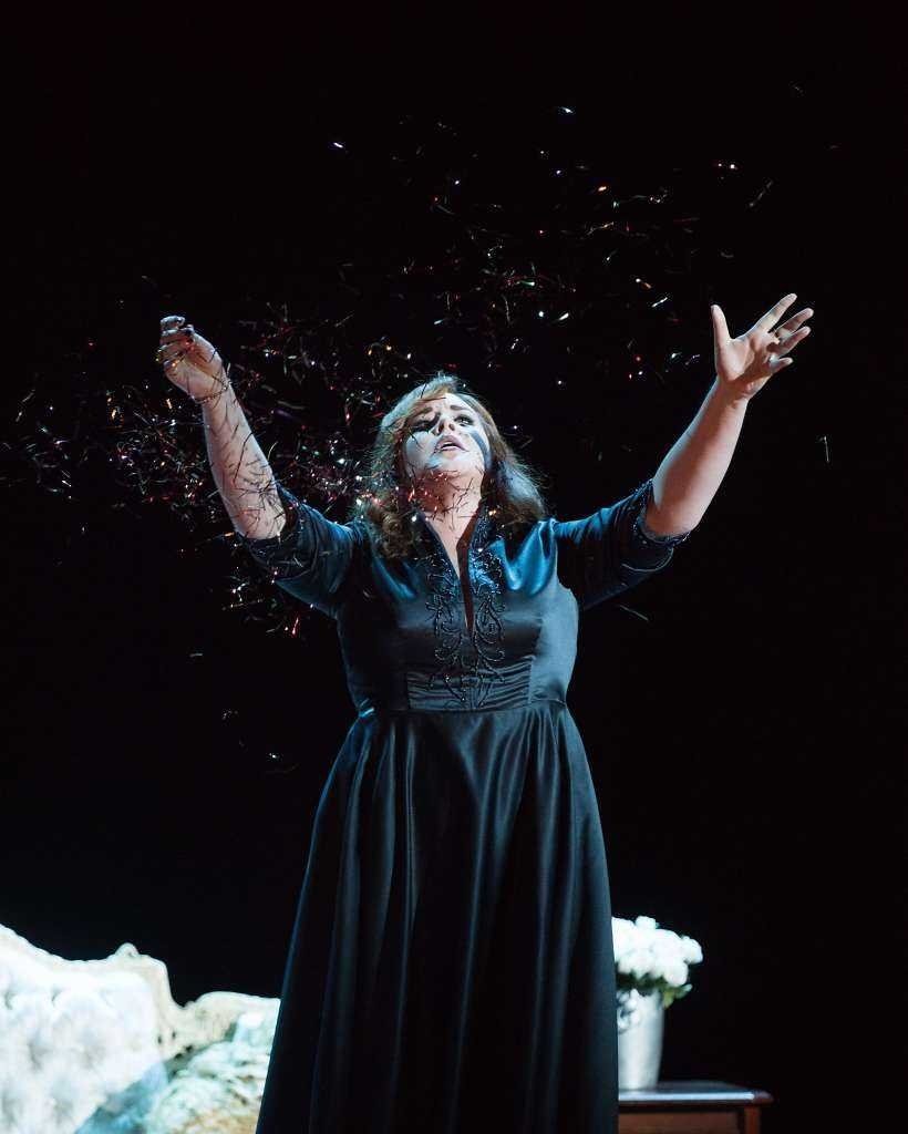 A scene showing a woman in a black dress throwing confetti in the air as part of The Merola Grand Finale (directed by Aria Umezawa).